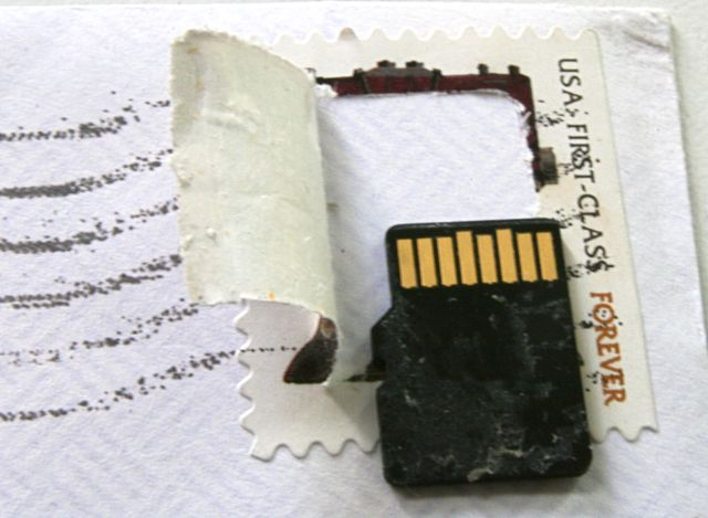 Postage stamp with a memory chip under it - cut open to reveal the stamp